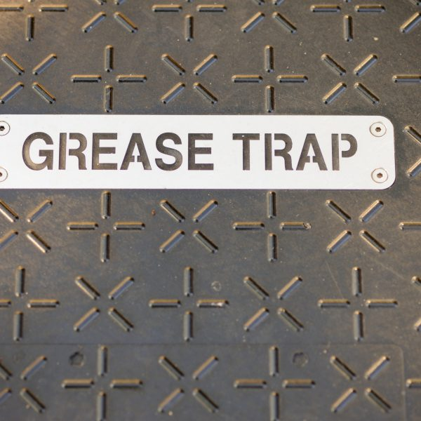 Close up photograph of stenciled metal great trap sign on metal cover on ground floor plate.  Plate has cross and plus sign pattern.